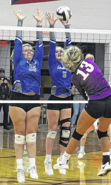 Washington's Haven McGraw (55) and Natalie Woods (5) go up for a block during a Frontier Athletic Conference match at McClain High School Tuesday, Sept. 28, 2021.