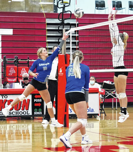 Washington's Kassidy Olsson (left) returns the ball over the net during a Frontier Athletic Conference match at Jackson High School Tuesday, Aug. 31, 2021. Also pictured for Washington is Calleigh Wead-Salmi.