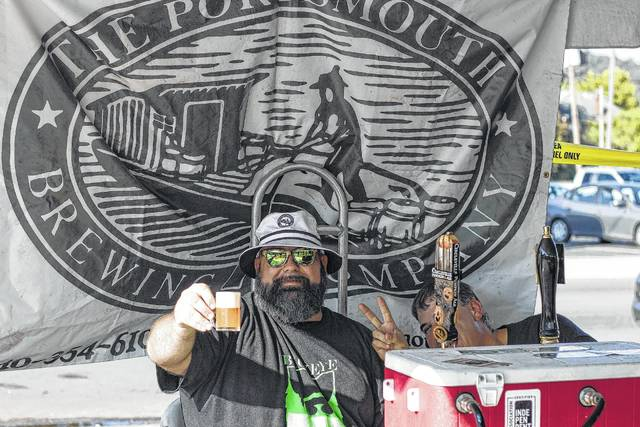 An individual holds up a craft beer at the 4th Annual River Valley Craft Beer Festival.