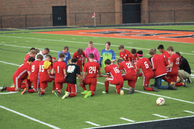 Minford players and coaches show a sign of unity before the game with a team prayer on the field