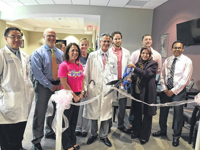 Wendi Waugh, Dr. Vincent Scarpinato, and staff cut ribbon at new Breast Cancer center.