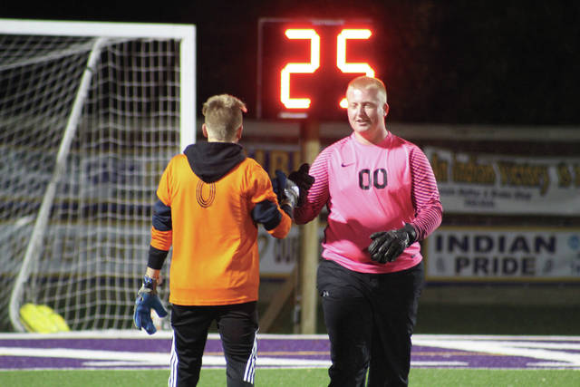 Wheelersburg's Dylan Burton gives a fist bump as he exits the field.