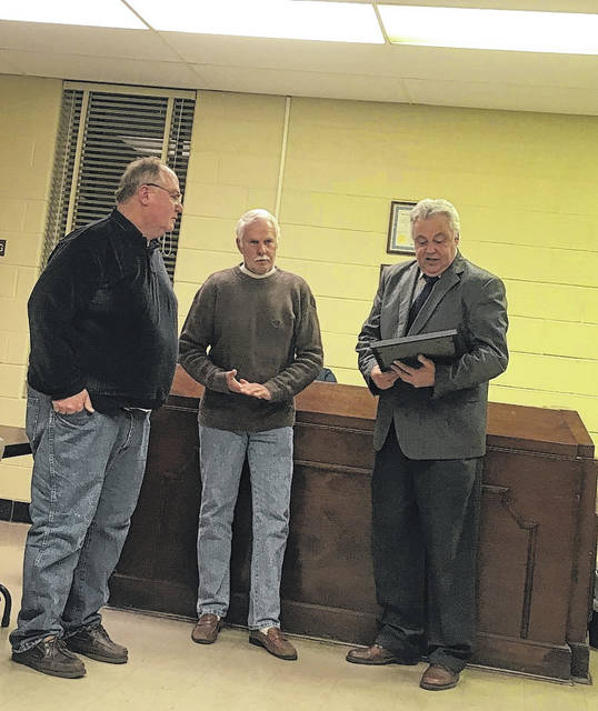 Ralph Imes and Vonald Patrick receiving plaques for their years of service from Junior Williams, Mayor