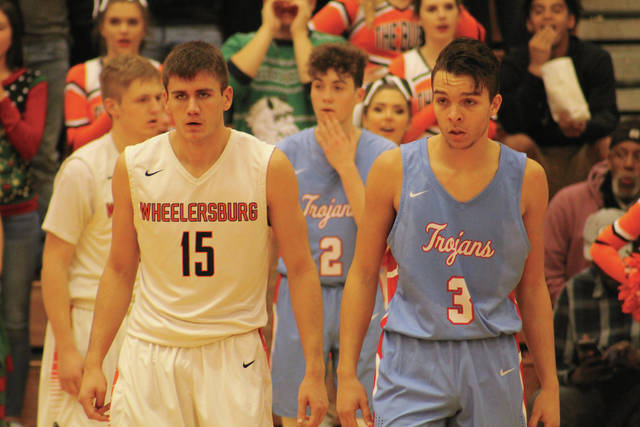 Wheelersburg's Mack Dyer and Portsmouth's Daniel Jordan watch the ball come up the court early in the game.