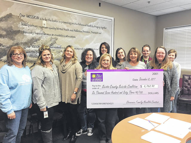 The Suicide Coalition accepted a check from Shawnee Family Health Center on Friday.