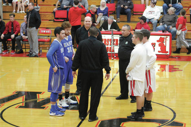 Captains from the East and South Webster boys basketball programs converge at halfcourt.