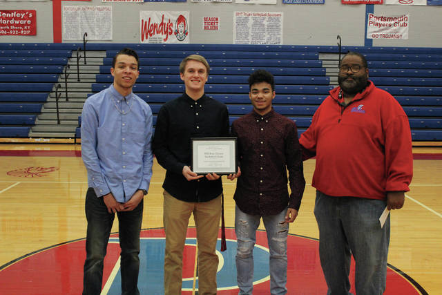 Portsmouth captains Daniel Jordan, Reese Johnson, and DJ Eley, along with Portsmouth head coach Gene Collins, pose with the certificate of excellence.