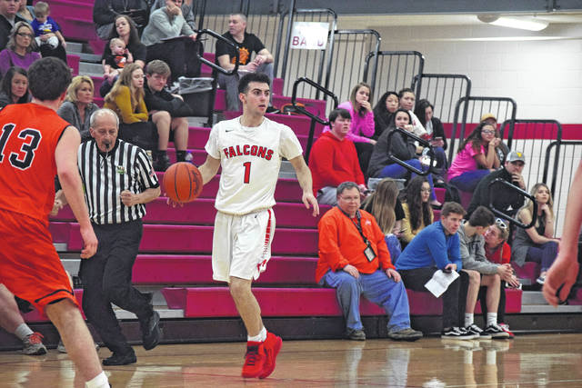 Minford's Kelton Kelley brings the ball up the floor for the Falcons.