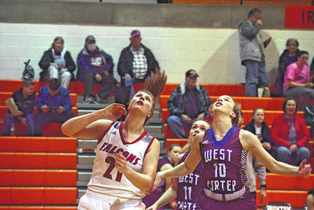 Minford's Ashley Blankenship and West Carter's Ragan Adkins watch as a ball gets ready to clang off of the rim on Saturday afternoon in Ironton.