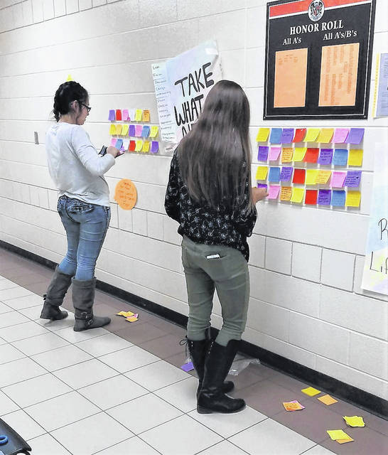 "Students place inspirational notes on the ""Wall of Positivity."""