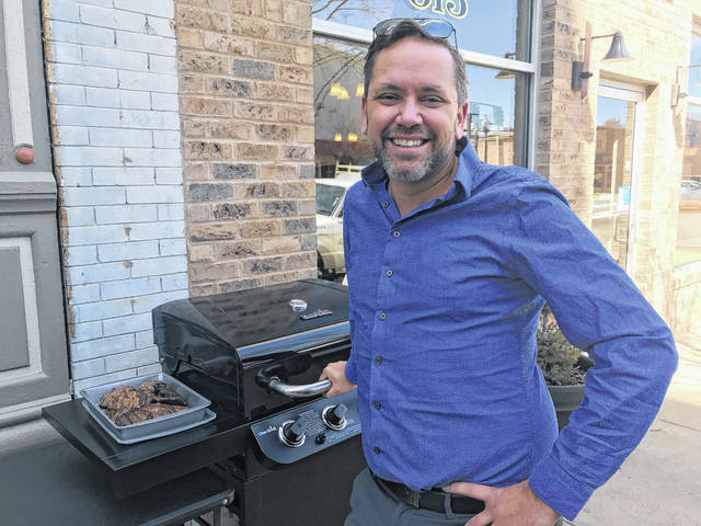 Sean Boldman of the Trinity Bussiness Group grills up some burgers for the ribbon cutting marking the opening of the newest company to move into the building he has renovated at 611 Chillcothe Street.