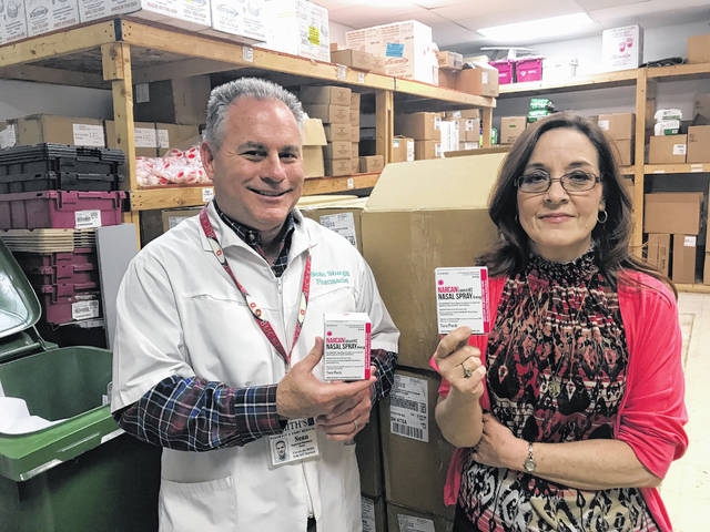 Sean Sturgill, owner of Smith's Pharmacy and Home Medical in Portsmouth, along with Lisa Roberts of the city health department, show off a free shipment of the drug Narcan, which can be used to save lives in instances of suspected opioid overdose.