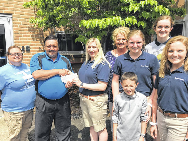 Notre Dame High School junior Alyssa Hiles (center in shorts) hands a check for the money she raised to benefit the Autism Project of Southern Ohio to project President Michael Bell. Joining the pair were (from left) Beth Swanner of the Autism Project, Subway restaurant owner Jamie Detwiller and her children, Claire, with arms on brother Camden (who has autism), Katie and Annie. All are Notre Dame students.