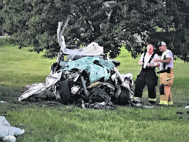 Emergency workers study the mangled remains of Zachary M. Strickland's Chevy Malibu following Thursday's crash.