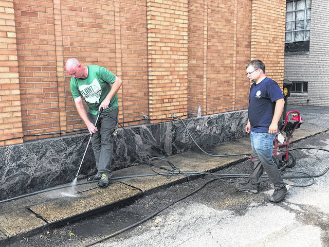 City worker Chris Tomlin operates a power washer outside the city health department on Friday. Health department worker Chad Wamsley looks on, waiting his turn with the washer.