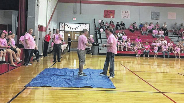 (Left to right on tarp) Aaron Franke, principal of Valley Jr. High and Jeremy Litteral, Superintendent of Minford Local School playing the egg game with Dennis Evans, principal of Minford Jr. High and Scott Rolfe, Superintendent of Valley Local schools looking on.