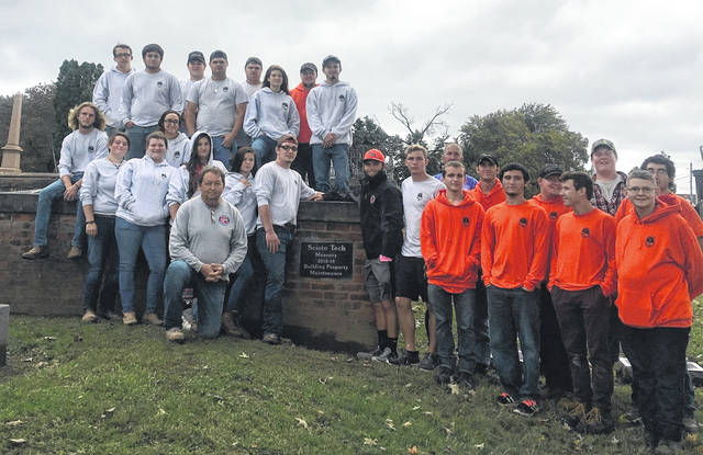 Larry Moore, center, and Chet Thayer back right, standing with their students and the plaque placed on the wall and gives them credit for rebuilding the wall at Greenlawn Cemetery