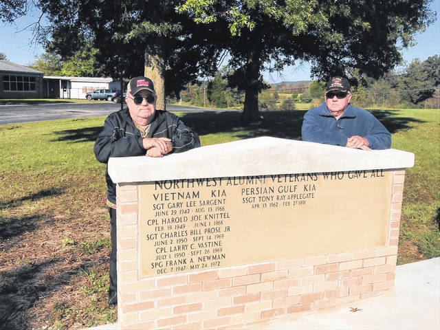Brothers Gene Johnson, left, and Ken Johnson, right, stand near the wall memorializing Northwest School District alumni killed in military action. Ken noted he is happy there is extra space on the wall.