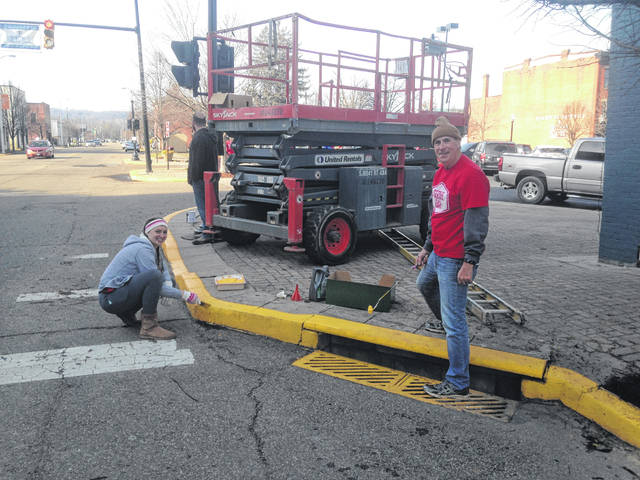 Tom Bennington and Ashley Hickman, both Life Point Church volunteers paint the curb at the edge of Second Street and Market Square. On this corner you will find Santa's Workshop and Candyland.