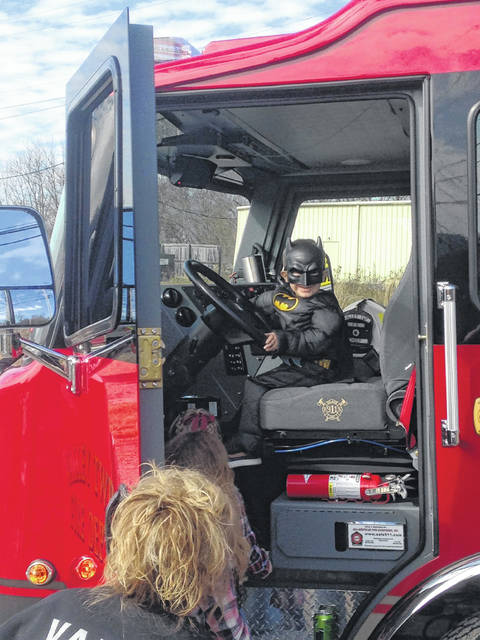 Jase Copas dressed in his Batman costume sounding the sirens on the Valley Township Fire Deparment's truck.