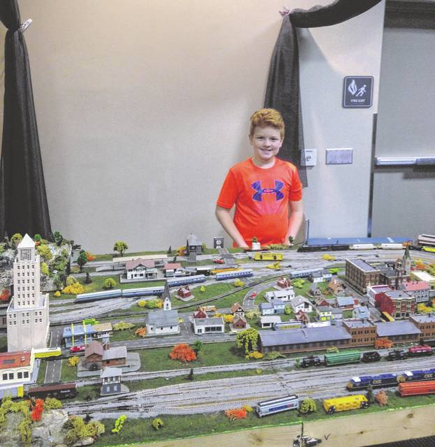 Youngest participant, Christopher Piccolo at his train display detailed with buildings and mountains.
