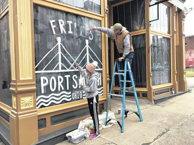Nick Sherman, on ladder, and wife Heather of Nick Sherman Design paint a logo and holiday images on what will be the first headquarters of the Friends of Portsmouth on Second Street.