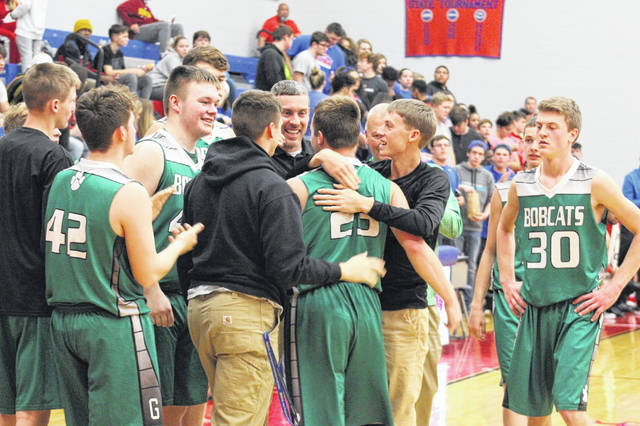 Green senior Tayte Carver was joined in celebration by his teammates after scoring his 1000th career point.