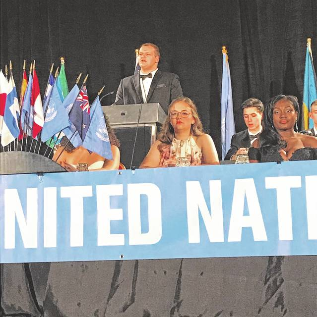 Jake Alley standing at the officers table, giving his speech in front of 1,500 people at the Ohio Model United Nations conference December 3.
