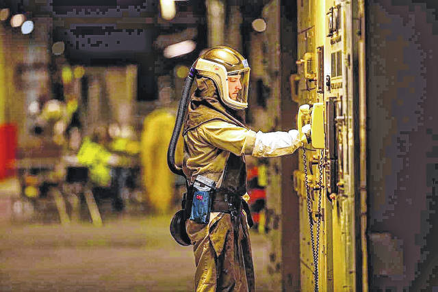 After a guided tour of the Piketon site last summer, FBP provided the <em>Daily Times </em>with photos such as this one of a worker in a haz-mat suit lookimg over some of the more complicated machinery in one of the plant's many buildings.