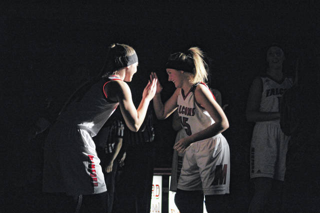 Minford's Livi Shonkwiler (right) greets teammate Brittany Wolfenbarker during player introductions before a game earlier this season.