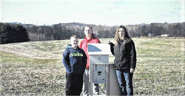 Piketon resident Elizabeth Lamerson and her sons near the air monitoring station she purchased because of concerns over operations at the Portsmouth A-plant visible in the background. Lamerson insists despite her concerns she does not want - and shouldn't need - to leave her family farm.