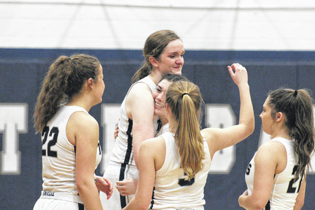 Notre Dame senior Katie Dettwiller embraces her teammates after scoring her 1,000th career point in Thursday's matchup with Eastern.