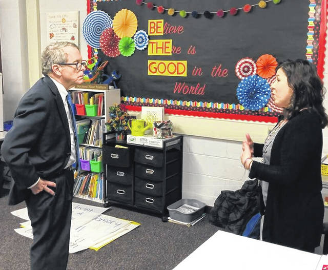 Teacher Kendra Cram with Governor DeWine discussing what was going on there in her classroom and both standing in front of a bulletin board that says Believe There is Good in the World and emphasis placed on BE THE GOOD.