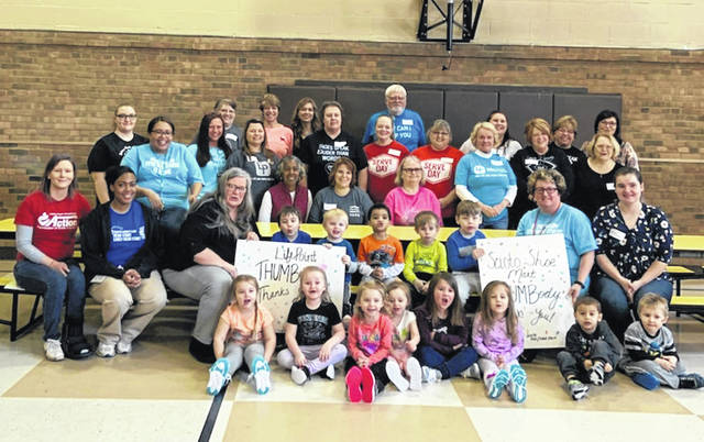 The many volunteers, teachers, helpers, and one of the groups of kids sporting their new shoes, with thank you signs for Scioto Shoe Mart for the shoes.