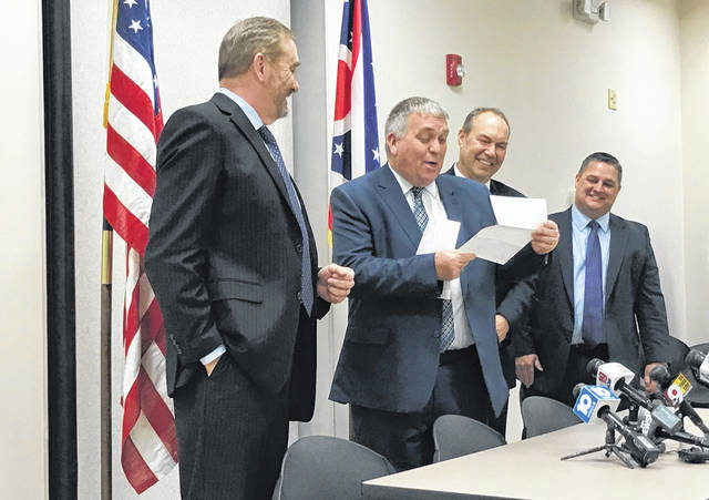 Pike County Prosecotor Rob Junk, second from left, is all smiles after Ohio Attorney General Dave Yost handed him a $100,000 check to help pay for prosecuting the Rhoden muders. Looking on are, from right, State Sen Rob Peterson, R-17, and State Rep. Shane Wilkin, R-91.