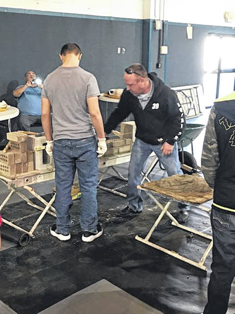 Luke Henry teaching a man how to set up and lay bricks at the jobs fair.