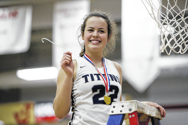 Notre Dame's Clara Hash poses for a photo after cutting a piece of the net, Thursday evening at Jackson High School.