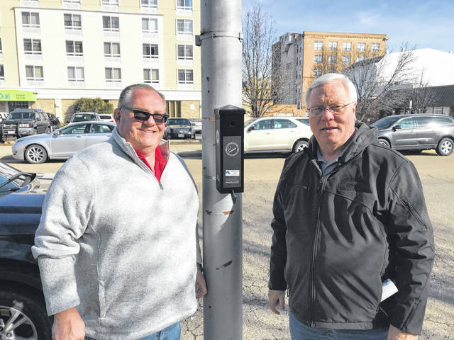 City Manager Sam Sutherland and LSSWMD Dan Palmer stand in front of newly installed cigarette butt container.