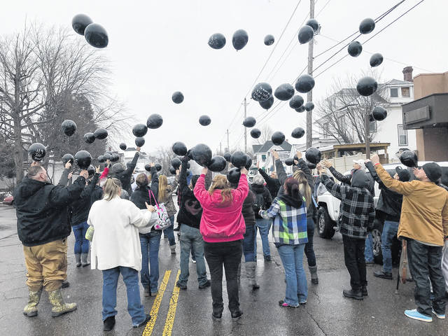 Port 45 clients, with their backs turned to the camera so as not to be so easily identified, along with center staff, release balloons honoring persons lost to substance abuse.