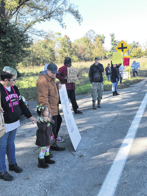 Protestors lineup along a school bus route near Minford Middle School in October.