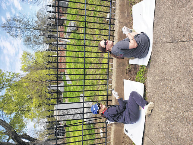 Regina Chabot and Jill Arnzen busy painting the fence at Greenlawn Cemetery Saturday afternoon.