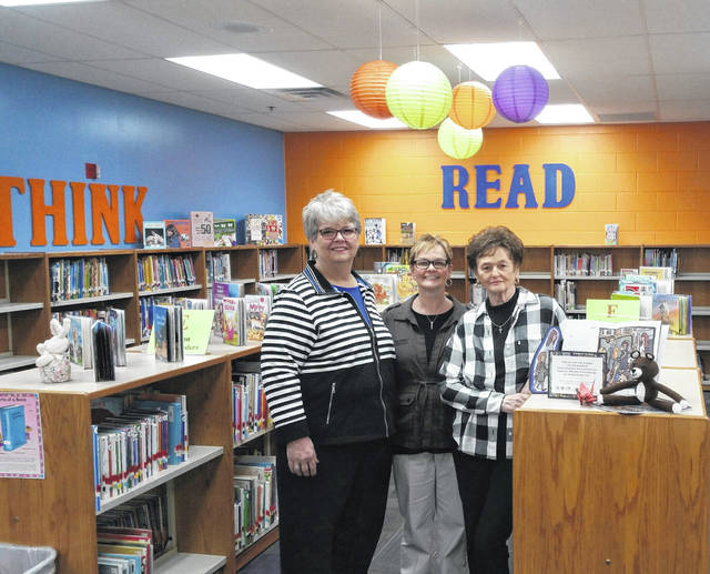 """PALS members Tess Midkiff (right) and Diana Wellman (left), along with """"<em>Bridge Lane</em>"""" co-author Jennifer Morgan (center), observe the new book that is displayed in the West Elementary School Library thanks to PALS and The Portsmouth Rotary Club."""