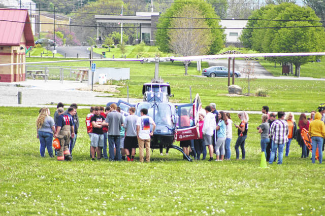 Students at West Portsmouth High School gather around a medical helicopter Thursday, as they watch a simulated life flight for the year's Prom Promise. West's prom is Saturday evening.