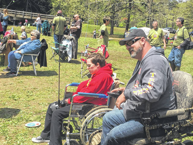 Sarah Neal, left, is assisted by Rick Bell, right, with her improvised rod holder attached to her leg. Neal has limited use of her arms from a car accident and would not be able to fish without the assistance of the rod holder. The two were part of the Duckworth True Lure Trout Derby Saturday at Roosevelt Lake in Shawnee State Park.