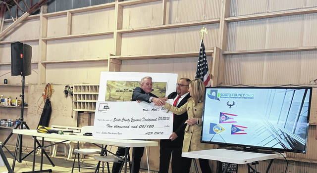 Liberty Shindel on right presenting the check to Scioto County Economic Development representatives.