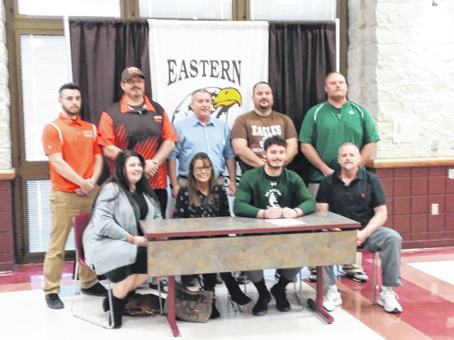 Eastern senior Jarett Bernthold signs with Wilmington College. Seated in front: Lakyn Davidson (sister), Kim Frazier (mom), Bernthold, and Roger Bernthold (dad). Back: Eastern Assistant Football Coach Seth Bledsoe, Eastern Head Football Coach Scott Tomlison, Eastern Superintendent Neil Leist, Eastern Assistant Football Coach Jeff Meier, and Assistant Football Coach Nolan Yates.