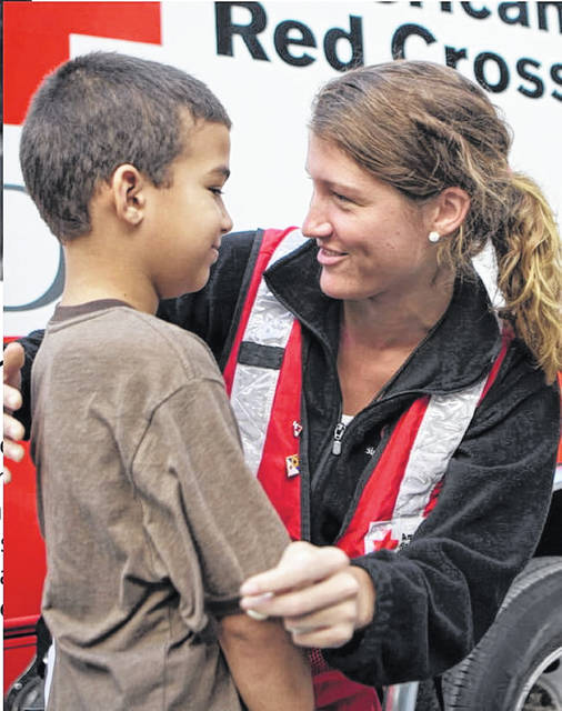 An American Red Cross volunteer speaking to a young man in disaster relief.