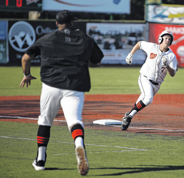 Wheelersburg junior Will Darling rounds third base as head coach Derek Moore ushers him on in the Pirates 11-1 win over Paint Valley.