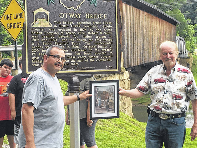 At left, Herb Irwin and Ken Riley, right, stand next to the plaque recently constructed at the Otway Covered Bridge. They are holding a picture with Irwin's grandmother and Riley's mother dedicating the plaque in 1962.