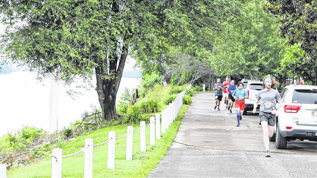Tyler Evans, 24, of Portsmouth, right, is shown on Riverside Drive in Russell as runners pass the Ohio River on the first leg of Run By The River.